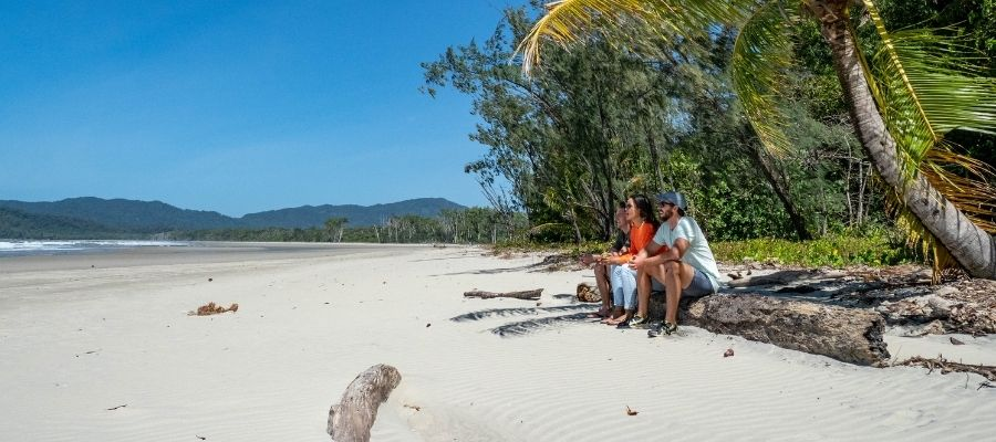 Friends sitting on beach overlooking Cape Tribulations beach