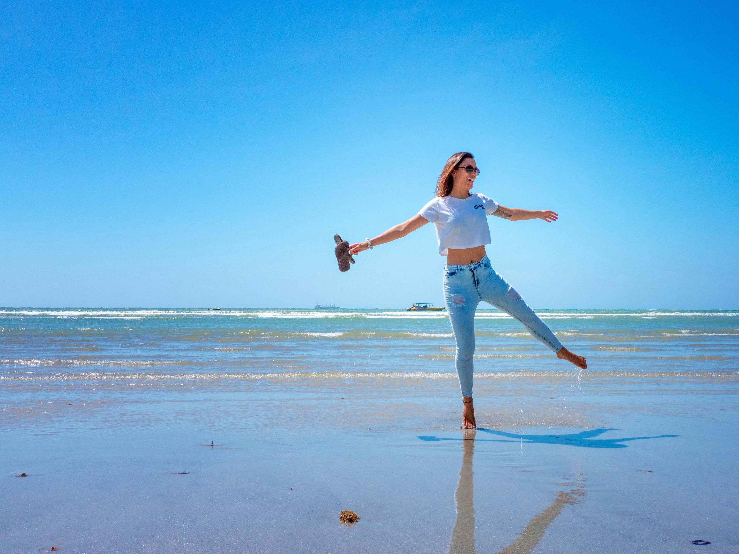 Woman dancing on beach at Cape Tribulation Port Douglas